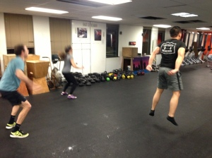 Members of the RRC getting in a quick AMRAP of jumping jacks, jump squats, and push ups pre-Rowing WOD